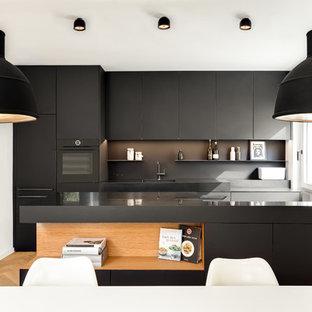 ミュンヘンのモダンスタイルのおしゃれなキッチン (フラットパネル扉のキャビネット、黒いキャビネット、黒いキッチンパネル、無垢フローリング、茶色い床) の写真