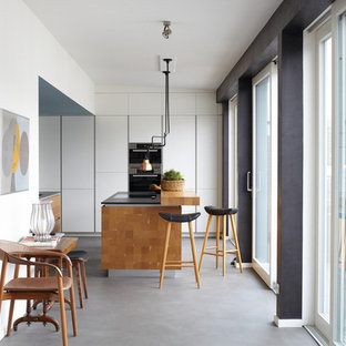 Offene, Mittelgroße Moderne Küche in L-Form mit flächenbündigen Schrankfronten, weißen Schränken, Küchengeräten aus Edelstahl, Vinylboden, zwei Kücheninseln und grauem Boden in Hamburg