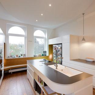 Große Moderne Küche in U-Form mit Einbauwaschbecken, flächenbündigen Schrankfronten, weißen Schränken, Küchengeräten aus Edelstahl, braunem Holzboden, Kücheninsel, braunem Boden und grauer Arbeitsplatte in Hamburg