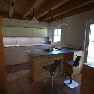 ミュンヘンの大きいコンテンポラリースタイルのおしゃれなキッチン (フラットパネル扉のキャビネット、白いキャビネット、人工大理石カウンター、グレーのキッチンパネル、ドロップインシンク、木材のキッチンパネル、白い調理設備、磁器タイルの床、赤い床) の写真