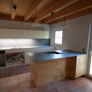ミュンヘンの広い地中海スタイルのおしゃれなキッチン (フラットパネル扉のキャビネット、白いキャビネット、人工大理石カウンター、グレーのキッチンパネル、ドロップインシンク、木材のキッチンパネル、白い調理設備、磁器タイルの床、赤い床) の写真