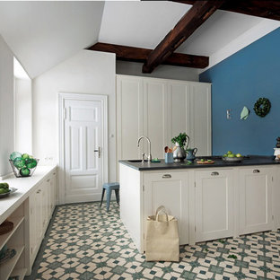 Large traditional enclosed kitchen inspiration - Large elegant porcelain tile enclosed kitchen photo in Dusseldorf with beaded inset cabinets, white cabinets, blue backsplash and a peninsula
