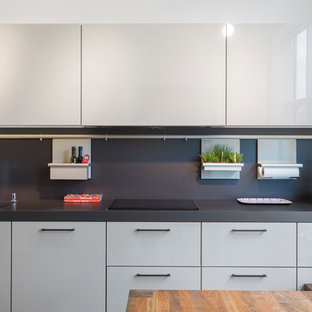Photo of a mid-sized contemporary galley eat-in kitchen in Hamburg with flat-panel cabinets, grey cabinets, laminate benchtops, black splashback, slate splashback, stainless steel appliances, marble floors, no island and grey floor.