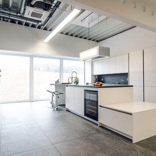 Zweizeilige, Offene, Geräumige Industrial Küche mit Kücheninsel, flächenbündigen Schrankfronten, weißen Schränken, Küchenrückwand in Schwarz, grauem Boden, grauer Arbeitsplatte und schwarzen Elektrogeräten in Frankfurt am Main