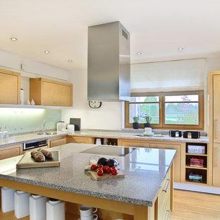 Idéer för ett mellanstort, avskilt skandinaviskt l-kök, med en undermonterad diskho, släta luckor, skåp i ljust trä, vitt stänkskydd, glaspanel som stänkskydd, integrerade vitvaror, bambugolv och en köksö