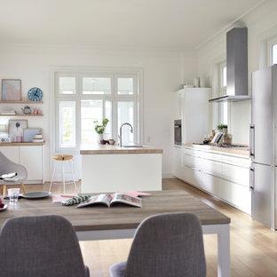 Offene, Zweizeilige, Große Skandinavische Küche mit Einbauwaschbecken, weißen Schränken, Arbeitsplatte aus Holz, Küchenrückwand in Weiß, Glasrückwand, Küchengeräten aus Edelstahl, hellem Holzboden, Kücheninsel, braunem Boden und flächenbündigen Schrankfronten in Hamburg