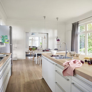 Large scandinavian open concept kitchen photos - Example of a large danish galley light wood floor and brown floor open concept kitchen design in Hamburg with a drop-in sink, white cabinets, wood countertops, white backsplash, glass sheet backsplash, stainless steel appliances, an island and flat-panel cabinets