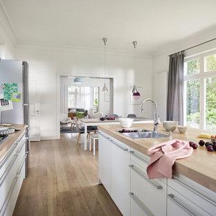 Offene, Zweizeilige, Große Nordische Küche Mit Einbauwaschbecken, Weißen  Schränken, Arbeitsplatte Aus Holz