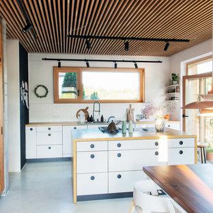 Zweizeilige Skandinavische Wohnküche mit Einbauwaschbecken, flächenbündigen Schrankfronten, weißen Schränken, Arbeitsplatte aus Holz, Küchenrückwand in Weiß, Betonboden, Kücheninsel, grauem Boden und brauner Arbeitsplatte in München