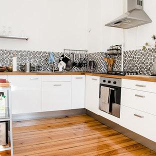 Idee per una cucina nordica chiusa e di medie dimensioni con lavello da incasso, ante lisce, ante bianche, top in legno, paraspruzzi grigio, paraspruzzi con piastrelle a mosaico, elettrodomestici in acciaio inossidabile e pavimento in legno massello medio
