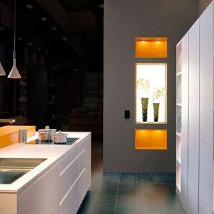 シュトゥットガルトの中くらいのコンテンポラリースタイルのおしゃれなキッチン (ドロップインシンク、フラットパネル扉のキャビネット、白いキャビネット、人工大理石カウンター、オレンジのキッチンパネル、木材のキッチンパネル、シルバーの調理設備、テラコッタタイルの床、茶色い床) の写真