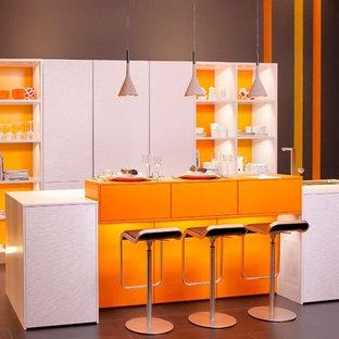 シュトゥットガルトの中くらいのコンテンポラリースタイルのおしゃれなキッチン (フラットパネル扉のキャビネット、テラコッタタイルの床、茶色い床、ドロップインシンク、白いキャビネット、人工大理石カウンター、オレンジのキッチンパネル、木材のキッチンパネル、シルバーの調理設備) の写真