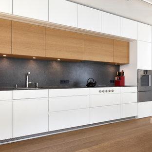 ミュンヘンの大きいコンテンポラリースタイルのおしゃれなキッチン (一体型シンク、フラットパネル扉のキャビネット、白いキャビネット、コンクリートカウンター、黒いキッチンパネル、メタルタイルのキッチンパネル、シルバーの調理設備の、無垢フローリング、アイランドなし、茶色い床、黒いキッチンカウンター) の写真