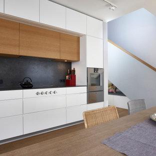 ミュンヘンの大きいコンテンポラリースタイルのおしゃれなキッチン (一体型シンク、フラットパネル扉のキャビネット、白いキャビネット、コンクリートカウンター、黒いキッチンパネル、メタルタイルのキッチンパネル、シルバーの調理設備、無垢フローリング、アイランドなし、茶色い床、黒いキッチンカウンター) の写真