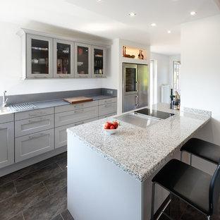 Zweizeilige, Große Moderne Wohnküche mit Einbauwaschbecken, profilierten Schrankfronten, grauen Schränken, Granit-Arbeitsplatte, Küchengeräten aus Edelstahl, Schieferboden, Halbinsel, schwarzem Boden und grauer Arbeitsplatte