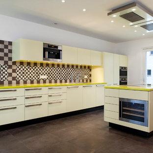 Offene, Einzeilige, Geräumige Moderne Küche mit Doppelwaschbecken, flächenbündigen Schrankfronten, gelben Schränken, bunter Rückwand, Rückwand aus Zementfliesen, Küchengeräten aus Edelstahl und Kücheninsel in Köln