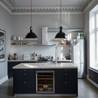 Mid-sized trendy galley brown floor and medium tone wood floor open concept kitchen photo in Hamburg with black cabinets, wood countertops, white backsplash, subway tile backsplash, stainless steel appliances, an island, an undermount sink, flat-panel cabinets and beige countertops