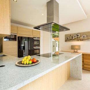 Mittelgroße Moderne Wohnküche in L-Form mit flächenbündigen Schrankfronten, Granit-Arbeitsplatte, schwarzen Elektrogeräten, Kalkstein, Halbinsel, Unterbauwaschbecken und hellen Holzschränken in Köln