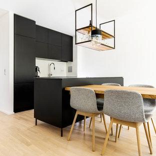 Offene, Zweizeilige, Mittelgroße Moderne Küche mit flächenbündigen Schrankfronten, schwarzen Schränken, hellem Holzboden, Kücheninsel und beigem Boden in München