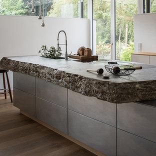 Große Moderne Küche in L-Form mit integriertem Waschbecken, flächenbündigen Schrankfronten, Kalkstein-Arbeitsplatte, Küchenrückwand in Weiß, Kücheninsel, grauen Schränken, hellem Holzboden und beigem Boden in München
