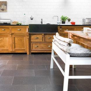 他の地域の中サイズのカントリー風おしゃれなキッチン (エプロンフロントシンク、レイズドパネル扉のキャビネット、中間色木目調キャビネット、白いキッチンパネル、サブウェイタイルのキッチンパネル、スレートの床、アイランドなし、黒い床、黒いキッチンカウンター) の写真