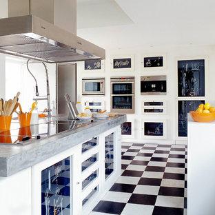 Mittelgroße Moderne Küche in L-Form mit profilierten Schrankfronten, blauen Schränken, Betonarbeitsplatte, Küchengeräten aus Edelstahl, Keramikboden, Halbinsel und grauer Arbeitsplatte in Sonstige