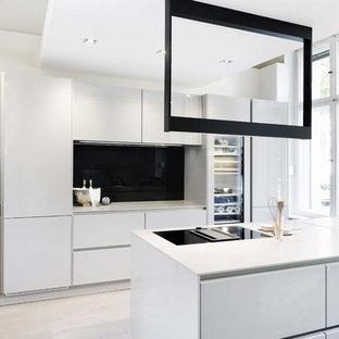 Zweizeilige, Mittelgroße Moderne Küche mit Einbauwaschbecken, flächenbündigen Schrankfronten, weißen Schränken, Küchenrückwand in Schwarz, Glasrückwand, schwarzen Elektrogeräten, hellem Holzboden, Halbinsel, beigem Boden und weißer Arbeitsplatte in Berlin