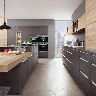 Moderne Wohnküche in L-Form mit Kücheninsel, flächenbündigen Schrankfronten, grauen Schränken, Küchenrückwand in Grau, schwarzen Elektrogeräten, Betonboden, beigem Boden und grauer Arbeitsplatte in Essen