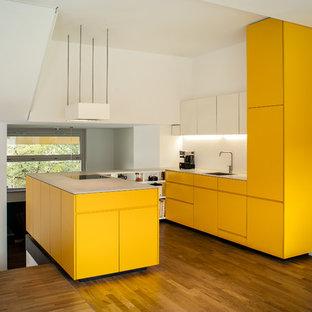 Idéer för ett mellanstort modernt grå kök, med en integrerad diskho, släta luckor, gula skåp, vitt stänkskydd, integrerade vitvaror, mellanmörkt trägolv, en halv köksö och brunt golv