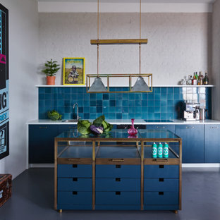 Photo of a small eclectic single-wall kitchen in Berlin with flat-panel cabinets, blue cabinets, glass benchtops, blue splashback, concrete floors, with island and window splashback.