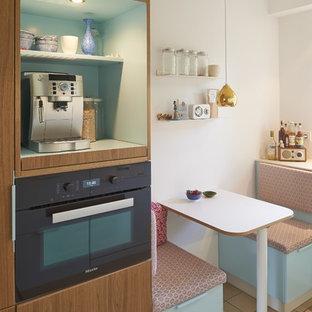 Kleine Nordische Wohnküche mit braunem Boden in Köln
