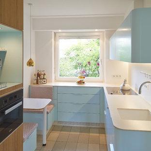 Geschlossene, Kleine Moderne Küche ohne Insel in U-Form mit integriertem Waschbecken, flächenbündigen Schrankfronten, blauen Schränken, Küchenrückwand in Weiß, schwarzen Elektrogeräten, beigem Boden und weißer Arbeitsplatte in Köln