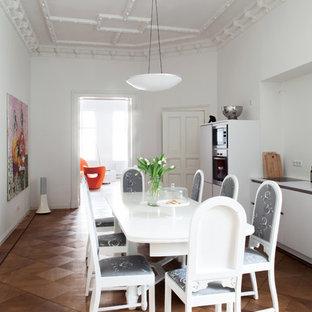 Foto de cocina comedor lineal, ecléctica, grande, sin isla, con suelo de madera en tonos medios, armarios con paneles lisos, puertas de armario blancas, salpicadero blanco y electrodomésticos de acero inoxidable