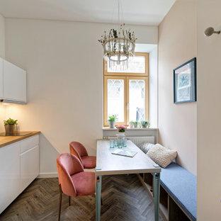 Einzeilige Moderne Wohnküche ohne Insel mit Einbauwaschbecken, flächenbündigen Schrankfronten, weißen Schränken, Arbeitsplatte aus Holz, dunklem Holzboden, braunem Boden und brauner Arbeitsplatte in München
