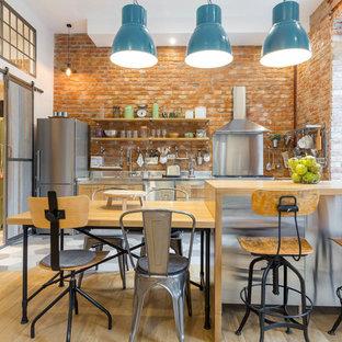 ヴェネツィアの中サイズのインダストリアルスタイルのおしゃれなキッチン (フラットパネル扉のキャビネット、中間色木目調キャビネット、ステンレスカウンター、レンガのキッチンパネル、シルバーの調理設備の、淡色無垢フローリング) の写真