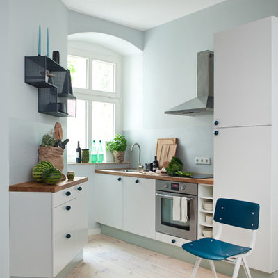 Kitchen - small contemporary light wood floor kitchen idea in Berlin with an undermount sink, flat-panel cabinets, wood countertops, glass sheet backsplash, no island, white cabinets, blue backsplash and stainless steel appliances