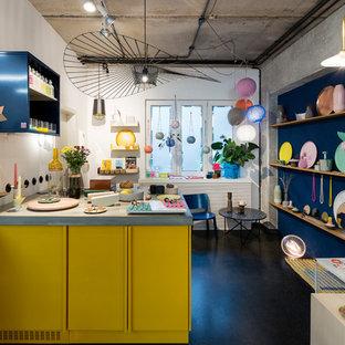 Geschlossene, Einzeilige, Mittelgroße Eklektische Küche mit Betonboden, Schrankfronten mit vertiefter Füllung, gelben Schränken, Halbinsel, schwarzem Boden und grauer Arbeitsplatte in Berlin