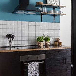 ベルリンの小さいコンテンポラリースタイルのおしゃれなI型キッチン (フラットパネル扉のキャビネット、濃色木目調キャビネット、木材カウンター、白いキッチンパネル、セラミックタイルのキッチンパネル、黒い調理設備、無垢フローリング、アイランドなし、茶色い床、茶色いキッチンカウンター) の写真