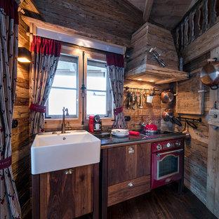 Diseño de cocina lineal, rústica, pequeña, sin isla, con fregadero sobremueble, armarios con paneles lisos, puertas de armario de madera en tonos medios, salpicadero marrón, salpicadero de madera, electrodomésticos de colores y suelo de madera oscura