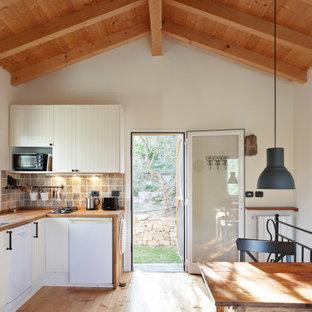 Ispirazione per la micro casa piccola beige mediterranea a due piani con rivestimento in stucco, tetto a capanna e copertura in tegole