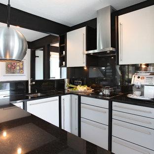 Moderne Küche in U-Form mit Unterbauwaschbecken, flächenbündigen Schrankfronten, weißen Schränken, Küchenrückwand in Schwarz und Küchengeräten aus Edelstahl in Sonstige