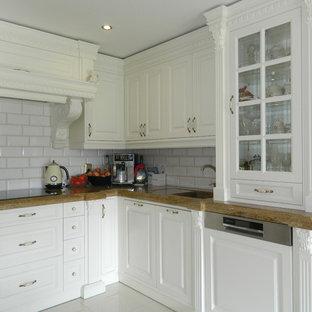 ハノーファーの小さいカントリー風おしゃれなキッチン (一体型シンク、レイズドパネル扉のキャビネット、白いキャビネット、木材カウンター、白いキッチンパネル、サブウェイタイルのキッチンパネル、白い調理設備、大理石の床、アイランドなし、白い床、茶色いキッチンカウンター) の写真