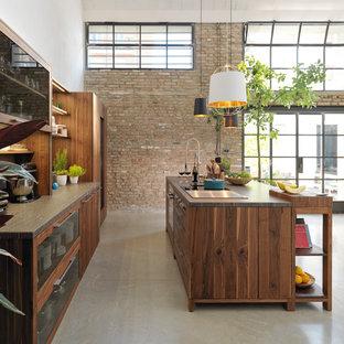 Offene, Große Industrial Küche mit Kücheninsel, Glasfronten, dunklen Holzschränken, Betonboden und grauem Boden in Hannover