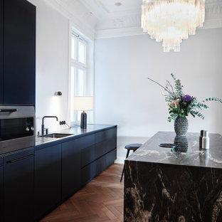 Zweizeilige, Mittelgroße Moderne Küche mit Unterbauwaschbecken, flächenbündigen Schrankfronten, schwarzen Schränken, Elektrogeräten mit Frontblende, Kücheninsel, braunem Boden und schwarzer Arbeitsplatte in Hamburg