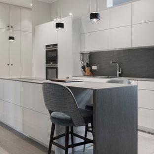 Mittelgroße Moderne Küche mit flächenbündigen Schrankfronten, weißen Schränken, Küchenrückwand in Grau, schwarzen Elektrogeräten, hellem Holzboden, Kücheninsel, beigem Boden und grauer Arbeitsplatte in Berlin