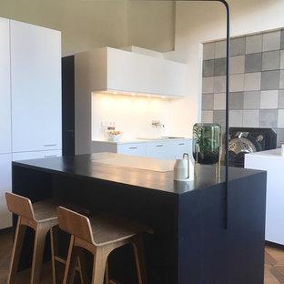 デュッセルドルフの大きいコンテンポラリースタイルのおしゃれなキッチン (シングルシンク、フラットパネル扉のキャビネット、白いキャビネット、木材カウンター、白いキッチンパネル、シルバーの調理設備、無垢フローリング、茶色い床、黒いキッチンカウンター) の写真