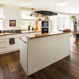 Moderne Wohnküche in L-Form mit Unterbauwaschbecken, flächenbündigen Schrankfronten, weißen Schränken, Arbeitsplatte aus Holz, dunklem Holzboden, Kücheninsel, braunem Boden und brauner Arbeitsplatte in Sonstige