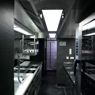 This is an example of a large industrial galley separate kitchen in Stuttgart with a drop-in sink, flat-panel cabinets, stainless steel cabinets, stainless steel benchtops, grey splashback, slate splashback, stainless steel appliances, concrete floors, with island and grey floor.