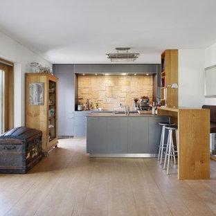 Offene, Zweizeilige Moderne Küche mit integriertem Waschbecken, flächenbündigen Schrankfronten, grauen Schränken, Mineralwerkstoff-Arbeitsplatte, Küchenrückwand in Beige, Küchengeräten aus Edelstahl, braunem Holzboden und Halbinsel in Berlin
