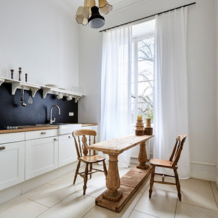 This is an example of a small traditional single-wall open plan kitchen in Frankfurt with an integrated sink, beaded inset cabinets, white cabinets, wood benchtops, black splashback, porcelain floors, beige floor and no island.